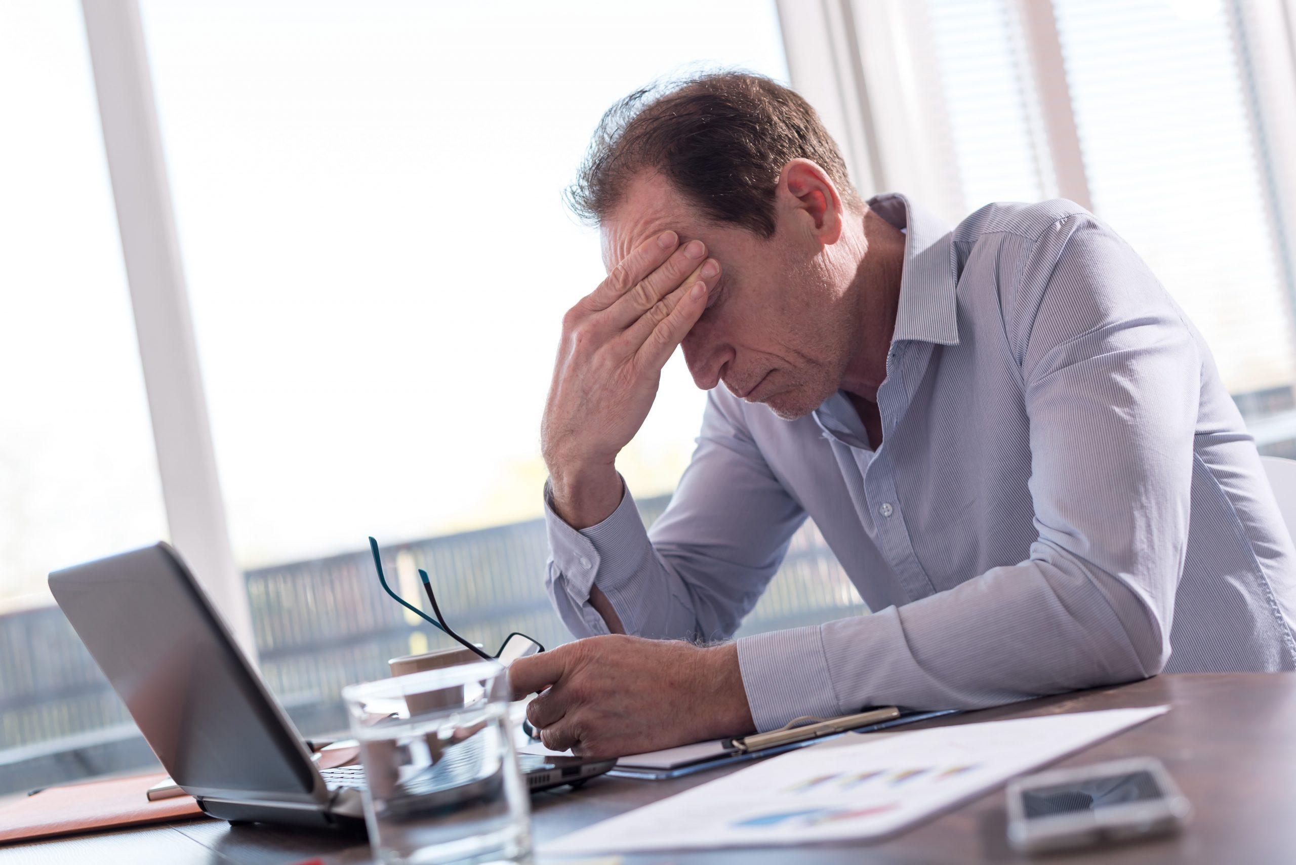 exhausted man staring at laptop